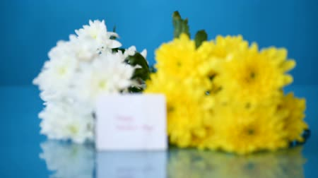 bouquet of white chrysanthemums with a greeting card for mom