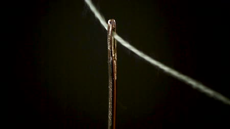 emperrado : thread stuck in a needle close-up on a black Vídeos