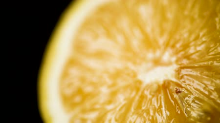 Lemon isolated on a black background. Fresh and Ripe halved lemon rotating