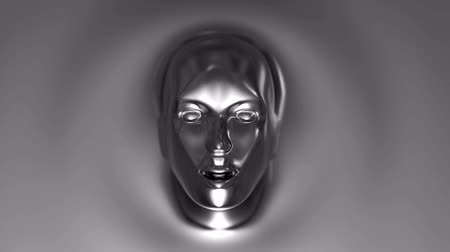 robot : Womans face, like the face of a robot from a liquid metal appears and disappears from the wall of the liquid metal Stock mozgókép