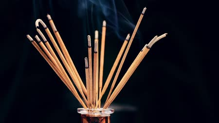 incenso : Close up of burning incense sticks with smoke over black background,rotating Stock Footage