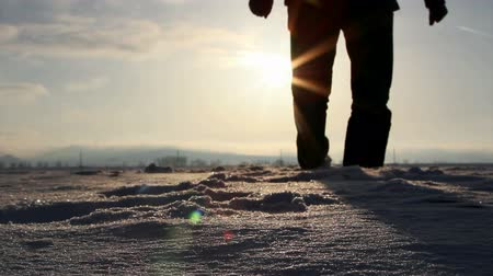 caminhada : Silhouette of a man walking in deep snow at sunset
