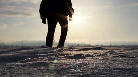 perdido : Silhouette of a man walking in deep snow at sunset