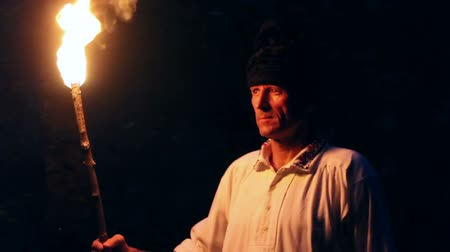 meşale : Closeup of a peasant searching through dark forest using a wooden torch Stok Video