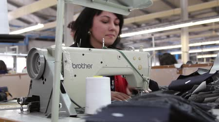 clothing : Women sew on a machine in a clothing factory