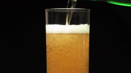 бутылки : Bottle filling a glass of beer on a black background