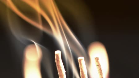 smell : Close up of burning incense sticks with smoke over black background Stock Footage