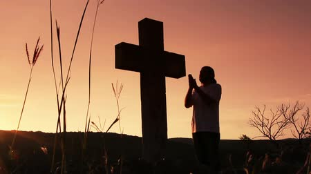 evangélium : Silhouette of man praying under the cross at sunsetsunsrise
