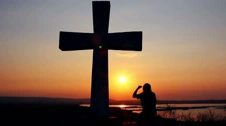 ibadet : Silhouette of man praying under the cross at sunsetsunsrise