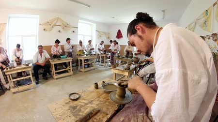 artesão : Luncavita, Romania - 16 June 2015: Craftsmens workshop. Craftsman shapes pottery on an classic potters kick wheel.