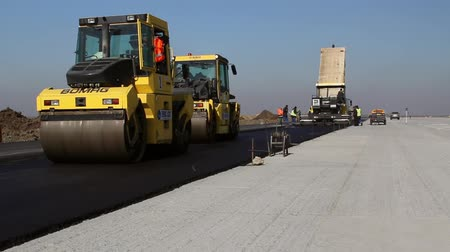 leveling : TULCEA, ROMANIA - OCTOBER 31: Road rollers leveling fresh asphalt pavement on a runway as part of the Danube Delta international airport expansion plan on October 31, 2015 in Tulcea, Romania.