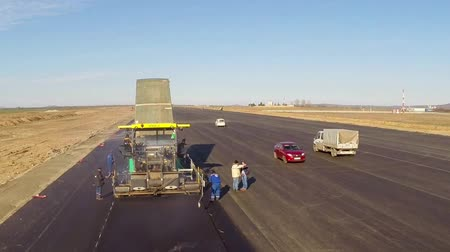 leveling : TULCEA, ROMANIA - DECEMBER 14: Tracked paver laying fresh asphalt pavement aerial view on a runway as part of the Danube Delta international airport expansion plan on December 14, 2015 in Tulcea, Romania.