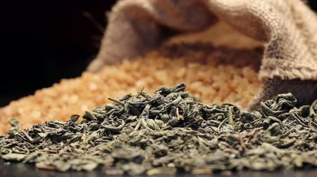tea bag : Brown sugar in gunny sack and a pile of dried green tea leaves, rotating