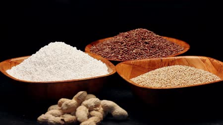 крахмал : Red rice,millet grains,tapioca pearls in small bowls and a pile of peanuts, rotating Стоковые видеозаписи