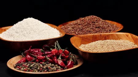перец чили : Red rice,millet grains,tapioca pearls in small bowls and a pile of dried chili, rotating