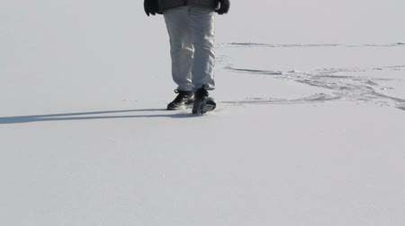 bota : Walking feet on a frozen lake Stock Footage