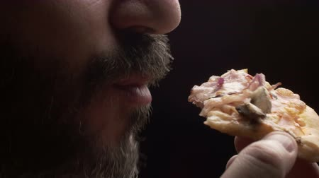 man eating : Close-up of a man eating a slice of pizza