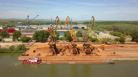 dockyard : TulceaRomania - May 23, 2018: Industrial cargo port with operating cranes on the Danube river, aerial view