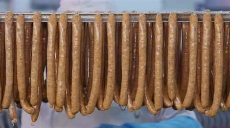 вкусности : Fresh sausages are placed on racks in a meat processing factory
