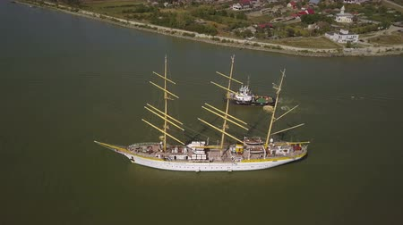 docking : Tulcea, Romania - 15 September 2019: Training ship Mircea sailing on the Danube, aerial view. Mircea is a A-class, bark type sailing vessel with three masts. Stock Footage