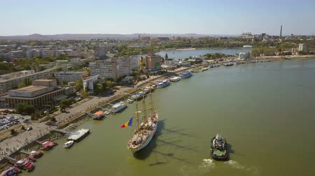 havlama : Tulcea, Romania - 15 September 2019: Training ship Mircea docking in Tulcea harbor, aerial view. Mircea is a A-class, bark type sailing vessel with three masts. Stok Video