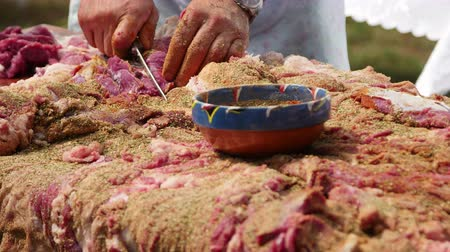 Farmer seasoning a whole lamb with a mix of herbs and salt before drying the meat Dostupné videozáznamy