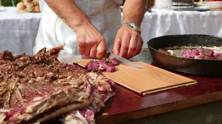 Farmer cutting (pastirma) air-dried spiced lamb meat into small pieces Dostupné videozáznamy