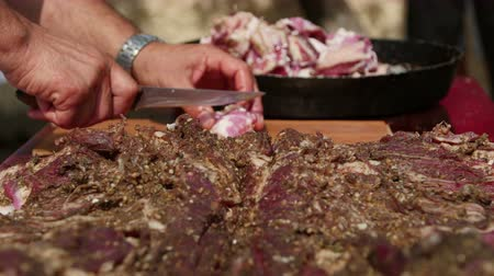 koyun : Farmer cutting (pastirma) air-dried spiced lamb meat into small pieces Stok Video