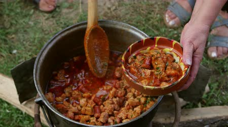servido : Homemade spicy pork stew with sausage cooked in a large metal pot