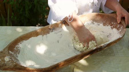 Housewife kneading dough in a wooden bowl