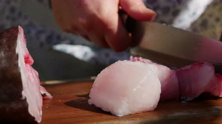 домохозяйка : Housewife cutting raw fish on a wooden chopping board Стоковые видеозаписи