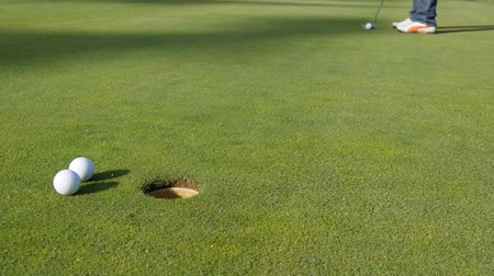 поле для гольфа : Young golfer putting golf ball into hole on a golf green.