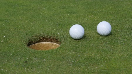close up shot : Close-up of golf ball going into the hole, then the golfer picks up the ball from the hole. Stock Footage