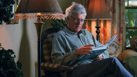 sending : Man Reads a Book in the Living Room at Home. Stock Footage