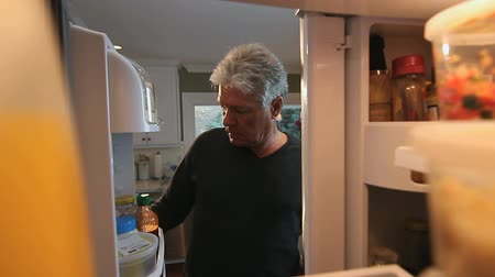 famished : Hungry Man Opens Refrigerator to Look for Something to Eat.  POV Stock Footage