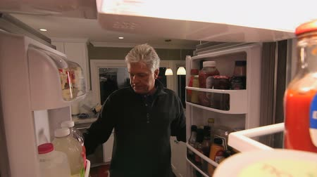famished : Man Opens Refrigerator To Look For Something to Eat.  POV.