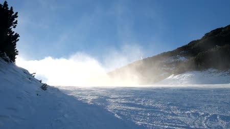 esqui : Snow making on slope. Skier near a snow cannon making fresh powder snow. Mountain ski resort and winter calm mountain landscape.