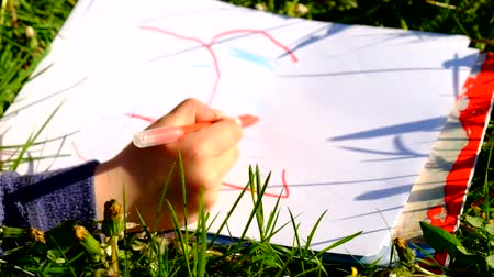 pontozás : Close up view of childs hand drawing colorful ornaments on paper. Notebook in fresh grass of meadow.