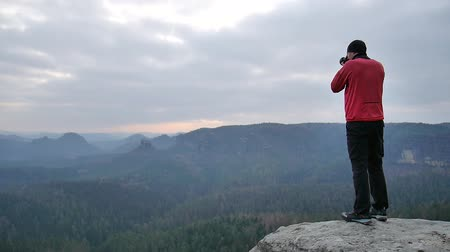 поход : Hiker in pink sportswear taking photos of misty morning landscape. Hike in rocks. Melancholic autumn morning. Стоковые видеозаписи