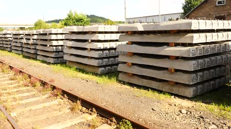 предъявитель : Sleepers stock in railway depot. Concrete railway ties Stored for reconstruction of old railway station. Old houses and highway bridge in background