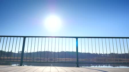 earpiece : Tall man with sunglasses, red cap and bue black sportswear is running at steel handrail on the bridge. Silhouette of sport active man running and exercising on the sunny blue sky background.