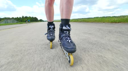 roller blading : Mans legs roller skating on asphal. Close up view to the fast moving of inline boots. Stock Footage