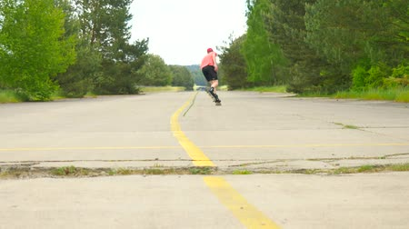 inclinado : Rear view to inline skater in green running singlet. Outdoor inline skating on an asphalt in the forest. Light skin man jumping on the road, moving with center of gravity. Stock Footage