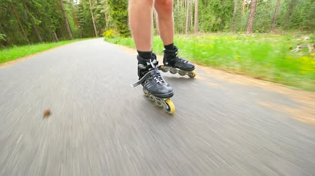 slowing : Shuffle skating and braking with t-style brake in park. Mans legs roller skating on the asphalt in hot summer day. Close up view to the quick shuffle movement of four wheels inline boots. Stock Footage