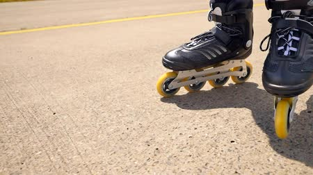přezka : Very close up view of working inline skates. Easy skating on the smooth asphalt. Close up view of the black four wheels inline boots. Dostupné videozáznamy