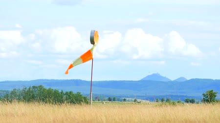field measurements : Wind sock fly. Summer hot day on private sports airport with abandoned windsock, wind is blowing and windsock is lazy moving