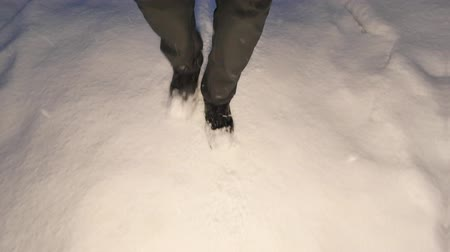 safeness : Man standing in dark trousers and high outdoor boots walking in snow while heavy snowing. Snow stormy night at forest path.