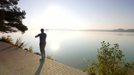 which : Sports man checking time on his sports watch. Runner at the mountain lake exercising against the evening sun. Stock Footage