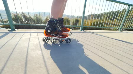přezka : Man standing on a light path. Outdoor inline skating. Close up view of a fast moving orange shell inline boots