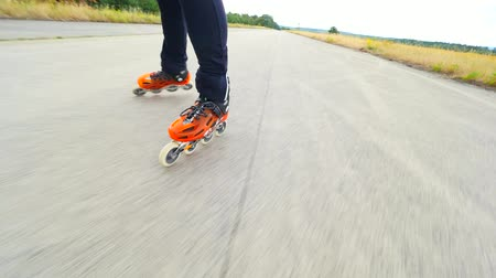 inline : Roller skating in summer. Hradcany airport, 9th of July, 2019, Orange hard shell rollerskates on asphalt on sunny day. Inline skating out of the city. Fun free time activity.